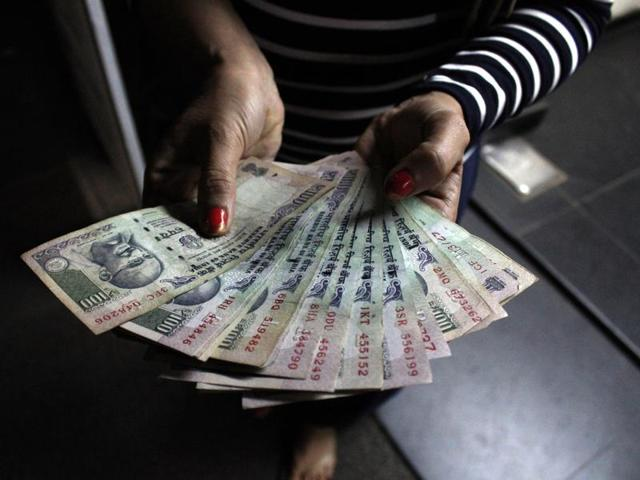 A woman shows Rs 100 notes withdrawn from an ATM in New Delhi on Tuesday.
