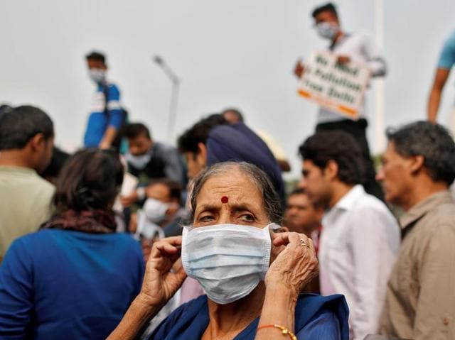 A man wears a mask to protect himself from the pollution as he drives a motorbike in Delhi.