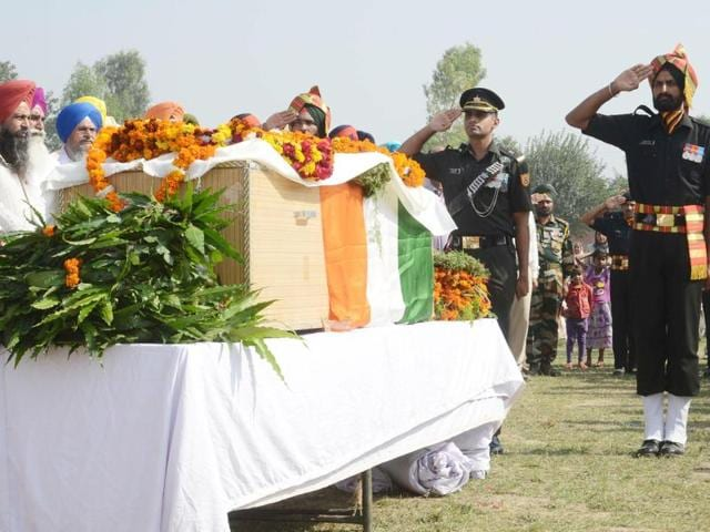 Security personnel and villagers paying their last respects to sepoy Gursewak Singh at his native village of Warana in Tarn Taran on Monday.