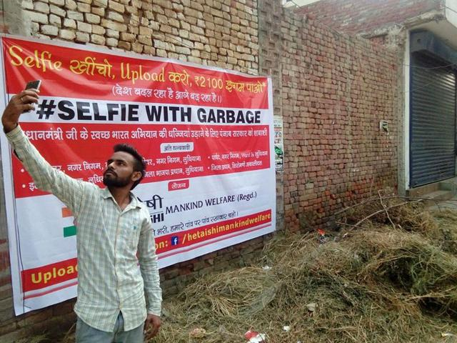 A man taking a selfie with garbage on Ferozepur road in Ludhiana on Monday.