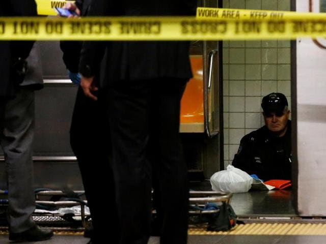 Members of the New York City police (NYPD) work at the scene after a commuter was pushed in front of a subway train as it arrived at Times Square station in New York City on Monday.