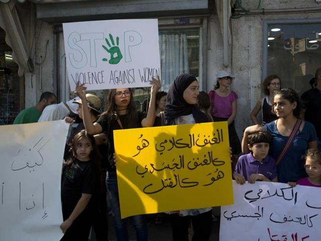 Israeli Arab women hold signs during a demonstration in Jaffa, Israel. Arabic sign reads:
