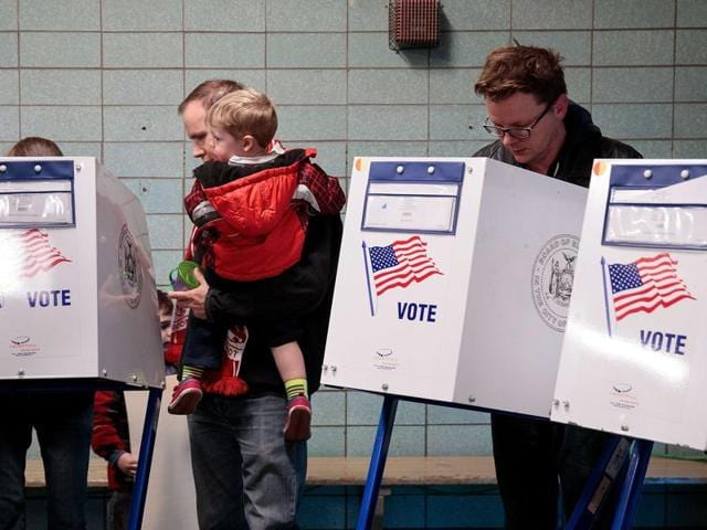 People vote at a polling site at Public School 261, November 8, 2016 in New York City. Citizens of the United States will choose between Republican presidential candidate Donald Trump and Democratic presidential candidate Hillary Clinton.