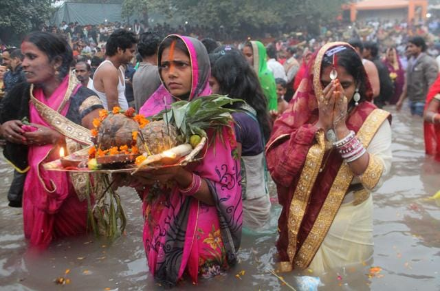 Devotees pray to the rising sun during Chhath puja at Sheetla Mata Temple pond on Monday.
