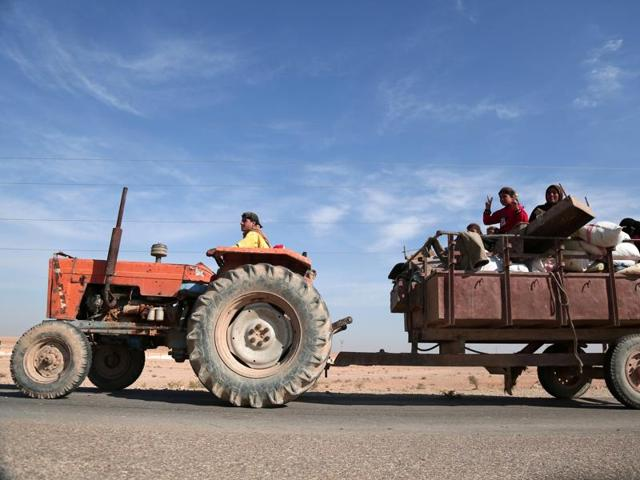 People fleeing areas of conflict ride a vehicle, north of Raqqa city.