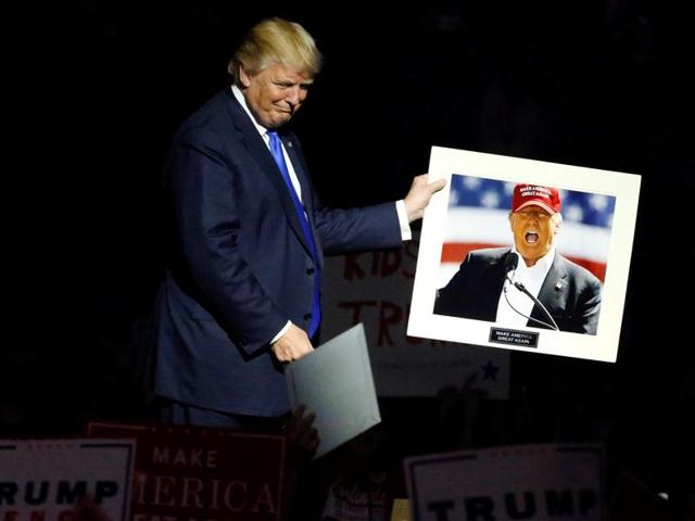 Republican US presidential nominee Donald Trump holds a picture of himself a supporter handed to him as he departs after rallying at an arena in Manchester, New Hampshire, US.