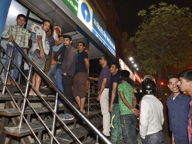 People waiting outside the ATM Machine at Defence Colony market in New Delhi on Tuesday
