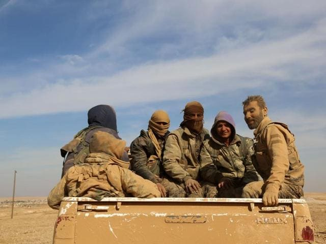 Syrian Democratic Forces (SDF), a US-backed Kurdish-Arab alliance, sit in the back of a truck in the village of Tal Aaj.