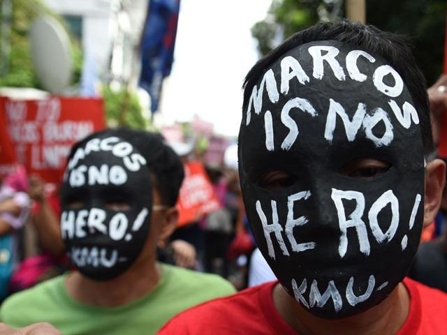 Activists wear masks with anti-Marcos slogans during a rally in front of the Supreme court in Manila on Tuesday.