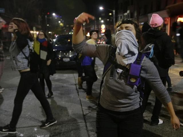 Protesters march past burned garbage in downtown Oakland, California. President-elect Donald Trump's victory set off multiple protests