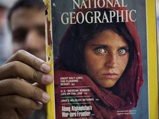 Pakistan's Inam Khan, owner of a book shop shows a copy of a magazine with the photograph of Afghan refugee woman Sharbat Gulla, from his rare collection in Islamabad, Pakistan, on October  26.