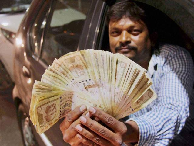 A man shows Rs 500 notes as the Prime Minister ordered to ban Rs 500 and Rs 1000 notes.