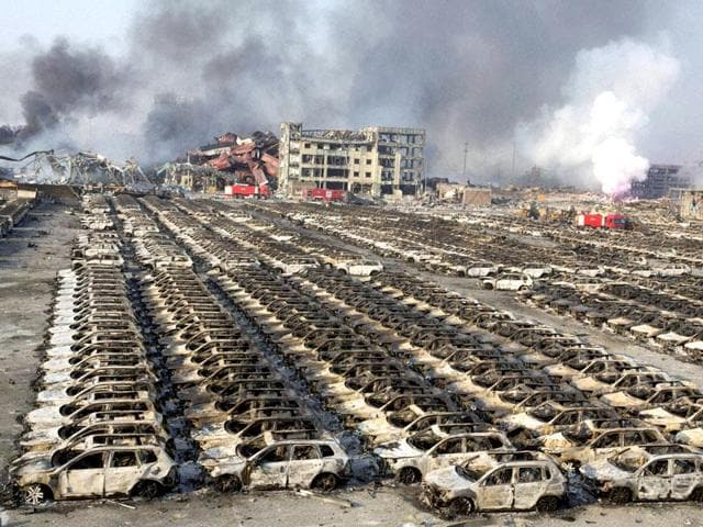 Smoke billows out from the site of an explosion that reduced a parking lot filled with new cars to charred remains at a warehouse in northeastern China's Tianjin municipality.