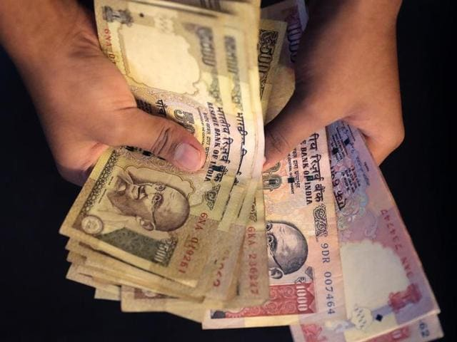 A person counts currency notes of 1000 and 500 denomination in New Delhi.(AP Photo)