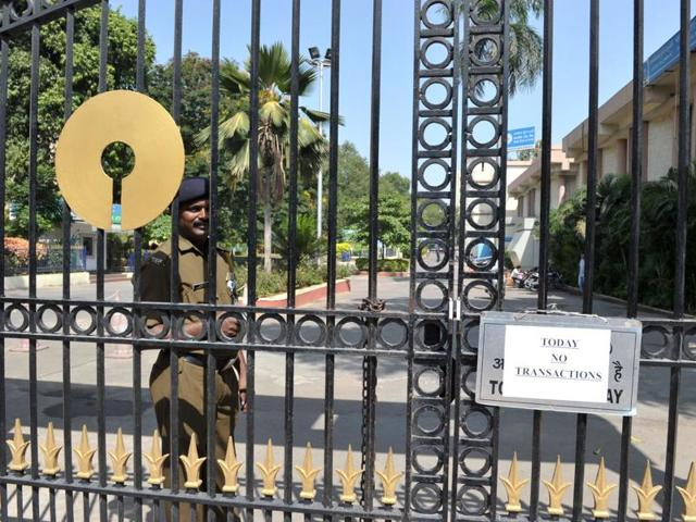 An Indian security guard stands at the entrance to The State Bank of India in Hyderabad on November 9.