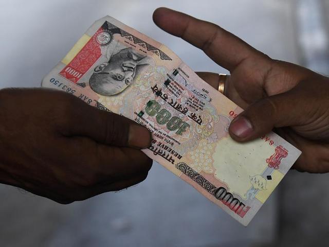 An Indian vehicle driver gives a 1000 rupee note to the Toll Plaza employee at the Nivedita Setu Toll plaza at Rajchandrapur on the outskirts of Kolkata.