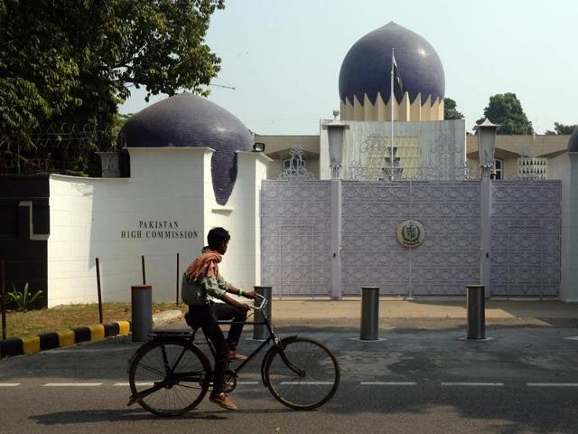 An Indian cyclist rides past the entrance to the Pakistan High Commission in New Delhi on October 27, 2016.