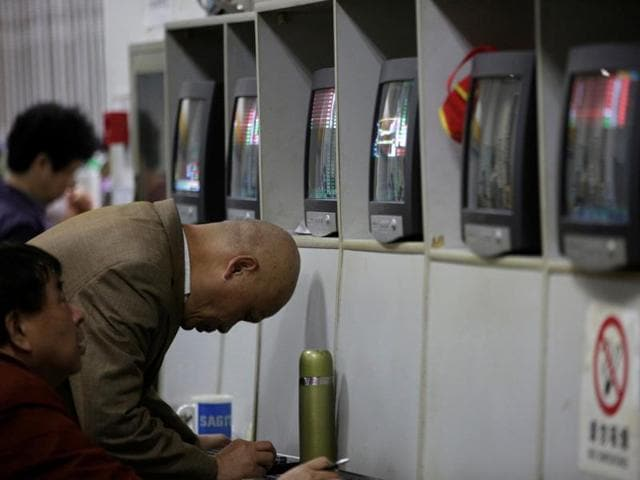 Investors look at screens showing stock information at a brokerage house in Shanghai, China.