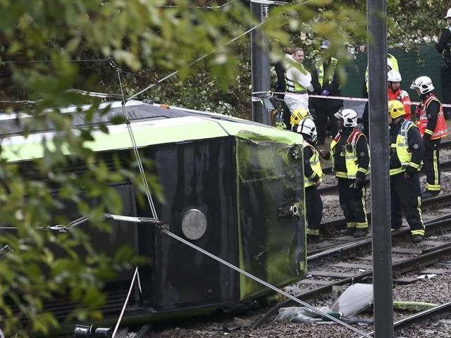 Members of the emergency services work next to a tram after it overturned injuring and trapping some passengers in Croydon, south London.
