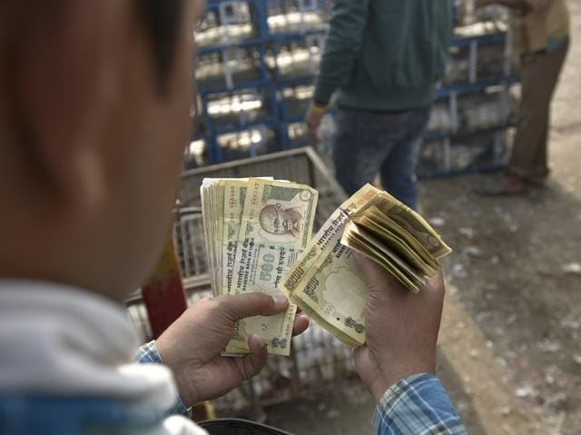 A man holds Rs.500 and Rs.1000 currency notes at Ghazipur chicken market in New Delhi.