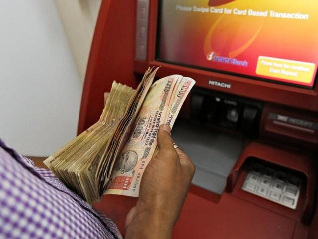 A customer deposits 1000 and 500 Indian rupee banknotes in a cash deposit machine at bank in Mumbai.