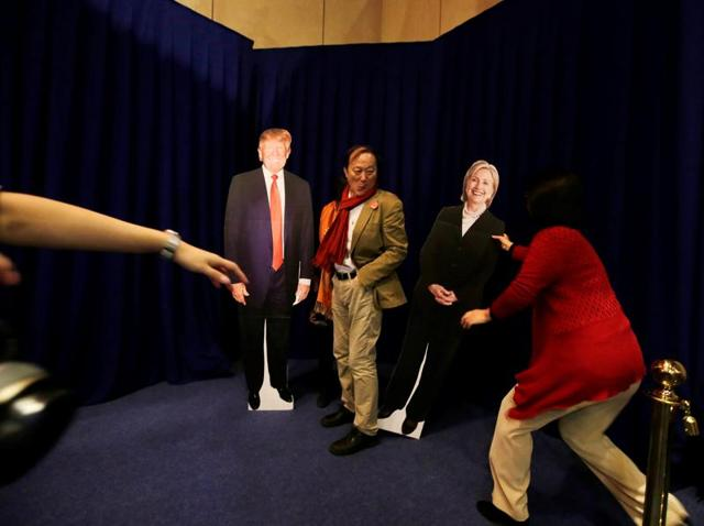 People pose with cardboard cutouts of presidential nominees Hillary Clinton and Donald Trump at an event held at the US embassy in Beijing on Wednesday.