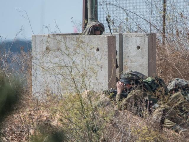 Israeli soldiers monitor an area along a border fence  near Metulla in northern Israel.