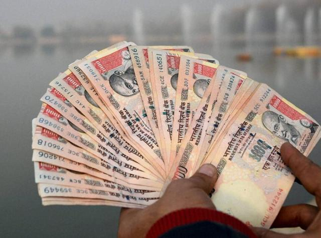A man displaying Rs 1000 notes after Central goverment ordered demonetisation of currency.