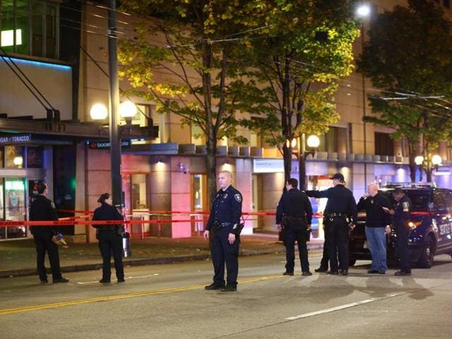 Law enforcement officers canvas the scene of a multiple victim shooting near Third Avenue and Pike Street in downtown Seattle.