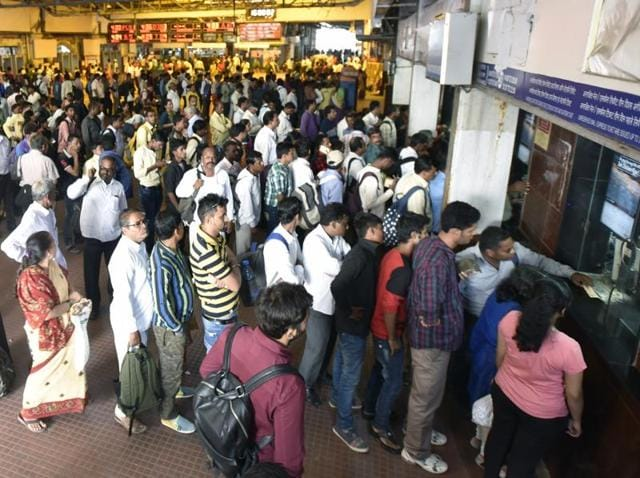 Travellers stand in a long queue at CST station in Mumbai on Wednesday.