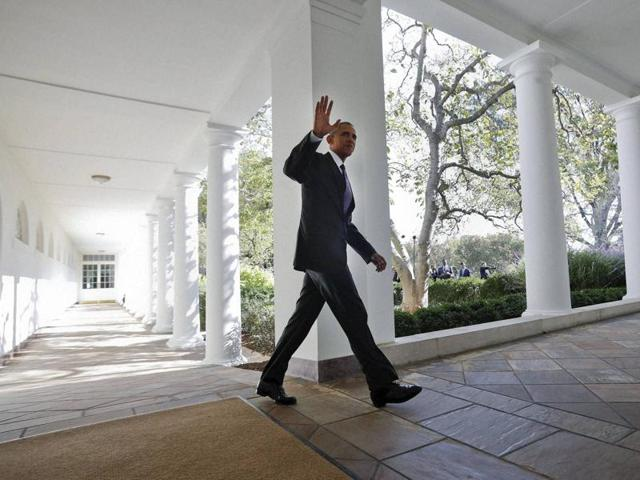 President Barack Obama waves as he walks down the White House Colonnade from the main residence to the Oval Office on Tuesday.