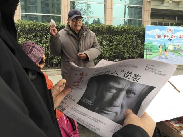 Zheng Gao of Shanghai, China, photographs the front pages of newspapers on display outside the Newseum in Washington on Wednesday, the day after Donald Trump won the presidency.