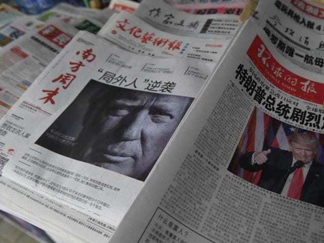 Chinese newspapers feature front page photos of US President-elect Donald Trump, at a news stand in Beijing on November 10, 2016.