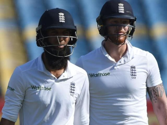 England's Ben Stokes (L) and Moeen Ali walk off the pitch.