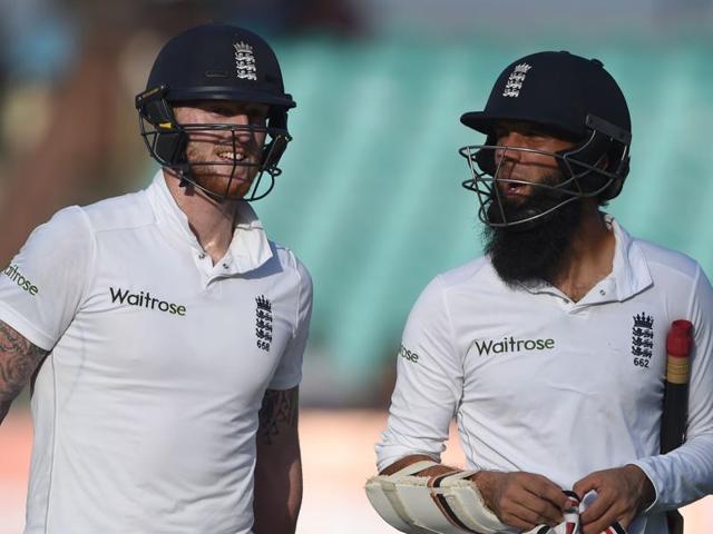 England's Moeen Ali (L) walks past teammate Ben Stokes.