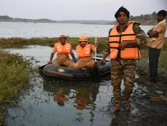 Actor Duniya Vijay (2R) walks from a boat with rescue officials as they search for two stuntmen in a reservior at Thippagondanahalli, some 35 kms west of Bangalore.Scuba divers have joined the search for the second stunt actor who drowned on Monday.