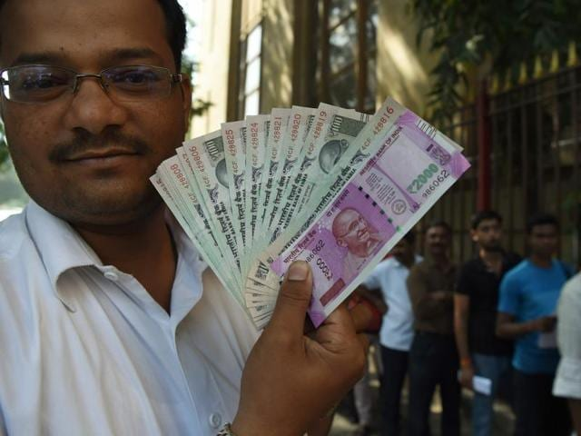 An Indian man displays a new 2000 and the old 100 rupee notes as he poses outside the Reserve Bank of India (RBI) in Mumbai.