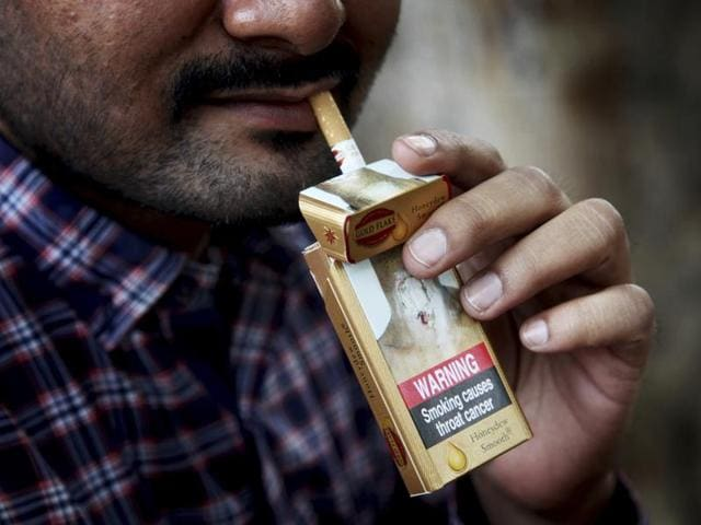 A man takes a cigarette from a pack in New Delhi, India.