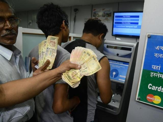 People queue to deposit money in a Cash Deposit Kiosk in Siliguri. Prime Minister Narendra Modi announced late November 8 that 500 and 1,000  rupee notes will be withdrawn from financial circulation from midnight, in a bid to tackle corruption.
