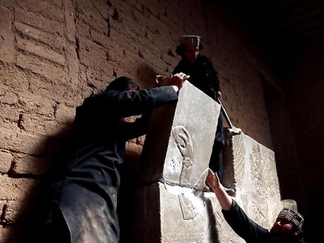 An image grab taken from a video made available by Jihadist media outlet Welayat Nineveh allegedly shows members of the Islamic State militant group destroying a stoneslab with a sledgehammer at what they said was the ancient Assyrian city of Nimrud in northern Iraq.