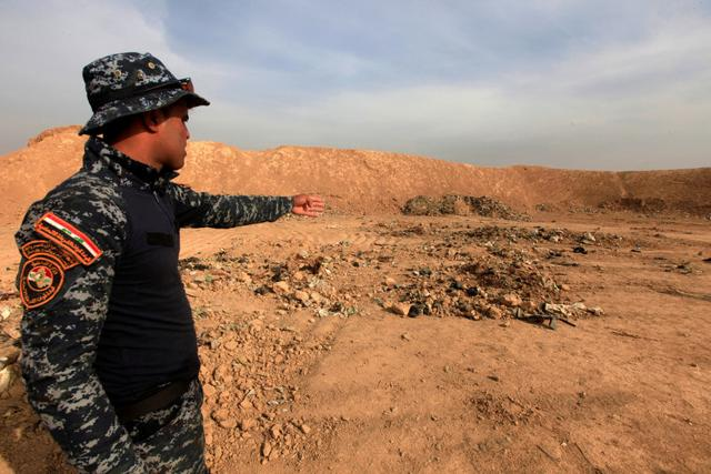 A member of Iraqi security forces gestures towards a mass grave for corpses in the town of Hammam al-Alil which was seized from Islamic State last week.