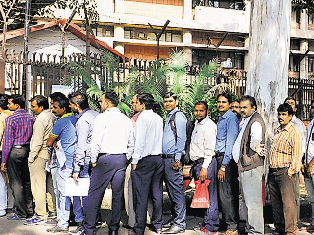 People queue up outside the RBI branch in Sector 17, Chandigarh, on Thursday, for depositing and withdrawing cash.