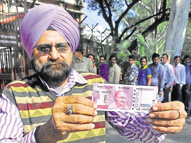 A cashier counts 500 and 1000 rupee notes inside a bank in Jammu, November 10, 2016