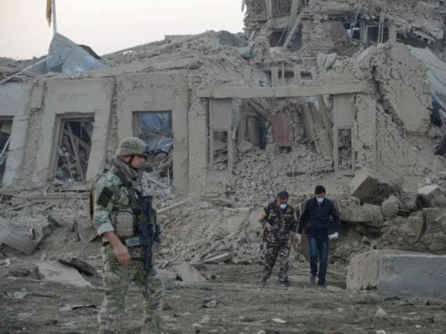 Afghan security forces and NATO troops investigate at the site of explosion near the German consulate office in Mazar-i-Sharif, Afghanistan.