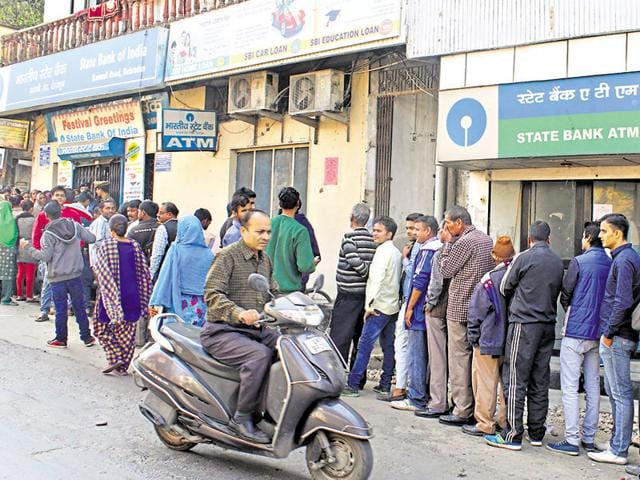 People stand in queue to deposit and exchange high-value banknotes outside a bank in Dehradun.