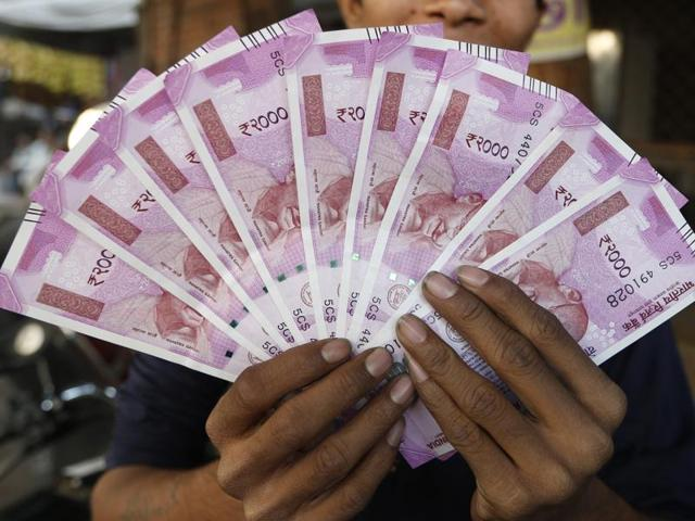 A man displays new currency notes of 2000 Indian rupee in Ahmedabad.