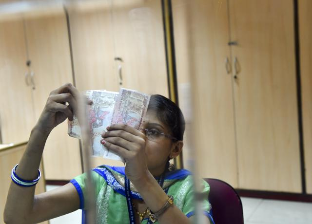 A bank staffer counts Rs 1000 notes at an SBI branch in New Delhi on Thursday.