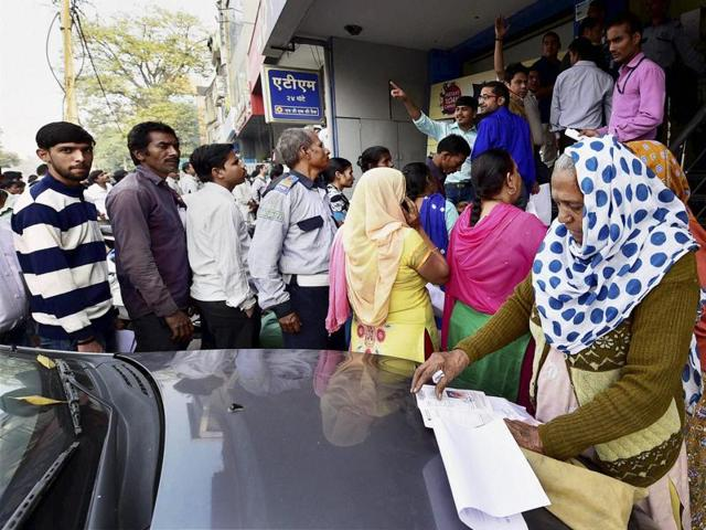 People queue outside Bank of India to exchange their old Rs 500 and 1000 notes in New Delhi on Friday.