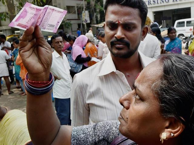 An Indian man displays new 2000 rupee notes outside the Reserve Bank of India (RBI) in Mumbai.