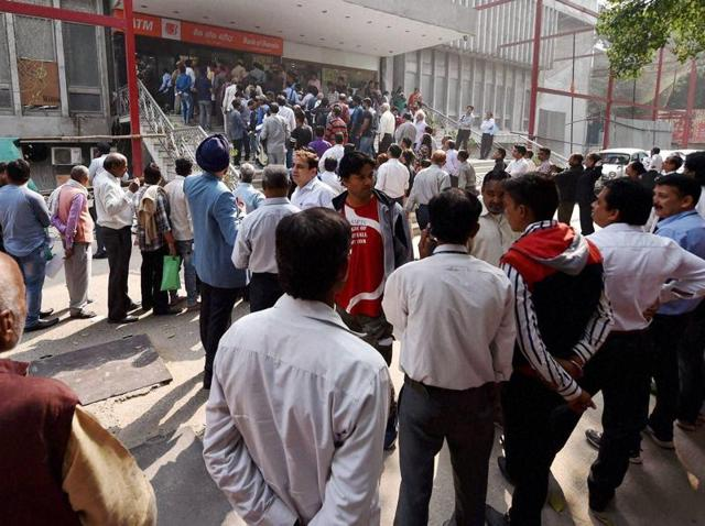 People stand in a queue outside a bank to exchange their old Rs 1000 and 500 notes in New Delhi.